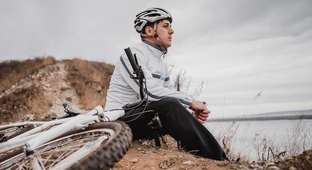 Homem sentado ao lado de sua mountain bike