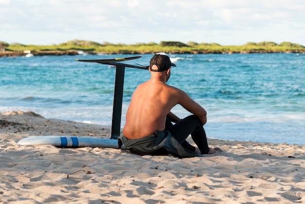 Homem sentado ao lado de sua prancha de surfe ao ar livre