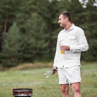Homem sentado ao lado de um churrasco tomando uma cerveja