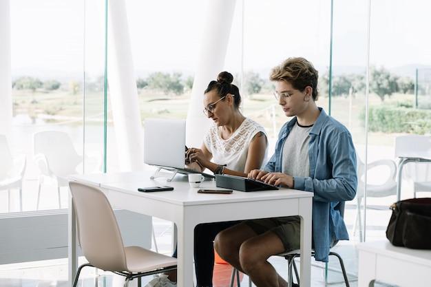 Homem sentado ao lado de uma garota na mesma mesa com laptops trabalhando em um coworking