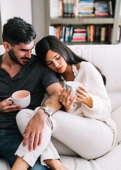 Homem sentado com a namorada segurando copos de café na mão