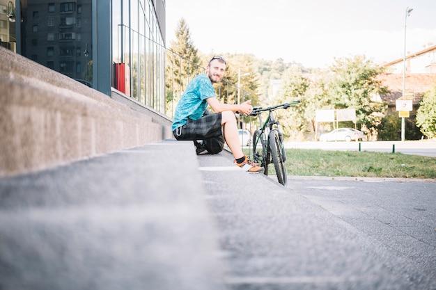 Homem sentado com bicicleta