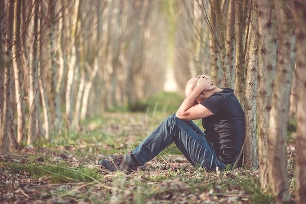 Homem sentado com depressão passando por uma fase difícil em sua vida, sofrendo de exaustão mental, ansiedade, esgotamento, conceito de saúde