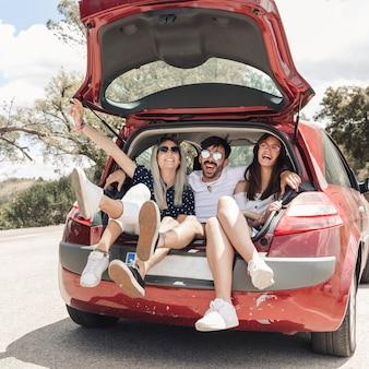 Homem sentado com duas amigas na mala do carro