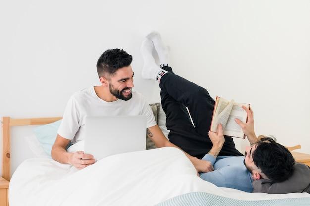 Homem sentado com laptop perto de seu namorado lendo o livro na cama