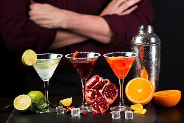 Homem sentado com os braços cruzados atrás de copos de cocktail coloridos