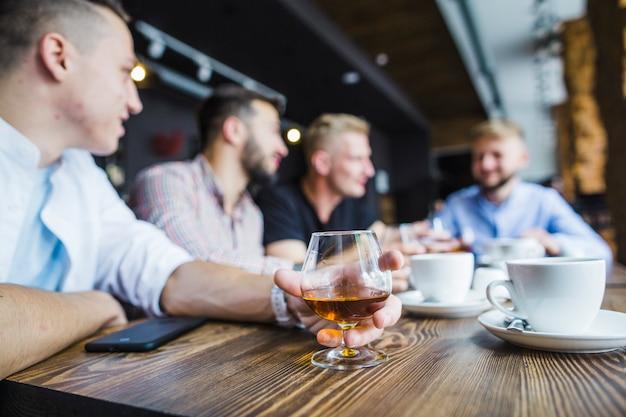 Homem sentado com seus amigos no restaurante segurando bebida
