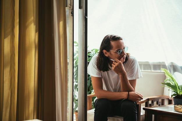 Homem sentado e fumando na varanda