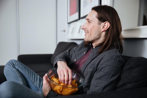 Homem sentado em casa dentro de casa comendo batatas fritas