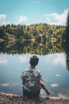 Homem sentado em frente a um lago sob um céu azul