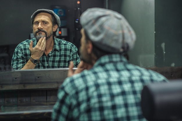 Homem sentado em frente ao espelho na barbearia