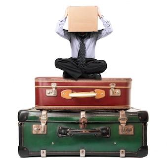 Homem sentado em malas