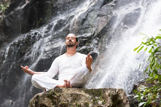Homem sentado em posição de lótus ioga na rocha sob uma cachoeira tropical e meditando