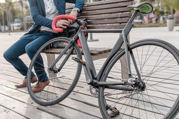 Homem sentado em um banco ao lado de sua bicicleta ao ar livre