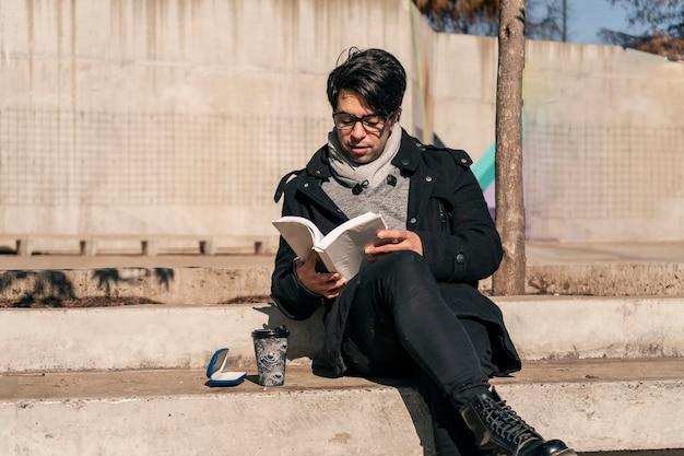 Homem sentado em um banco de concreto em um parque público, lendo um livro e tomando uma bebida quente ao sol.