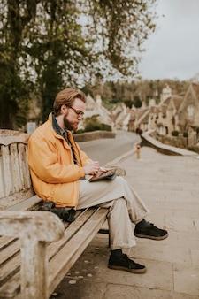 Homem sentado em um banco e trabalhando em um tablet na aldeia