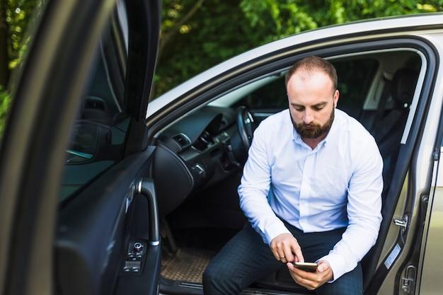 Homem sentado em um carro com a porta aberta, olhando para a tela do telefone móvel