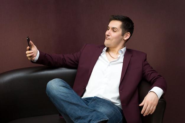 Homem sentado em um sofá tomando um self