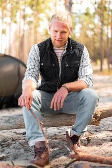 Homem sentado em uma árvore caída de frente