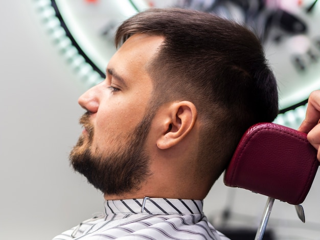 Homem sentado em uma barbearia