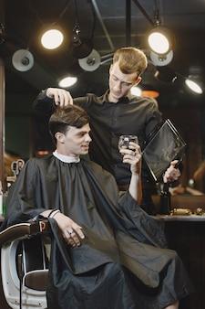 Homem sentado em uma cadeira. cabeleireiro com um cliente. cara bebendo um uísque.