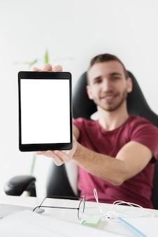 Homem sentado em uma cadeira de jogos e mostrando seu tablet