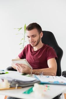 Homem sentado em uma cadeira de jogos, olhando suas anotações