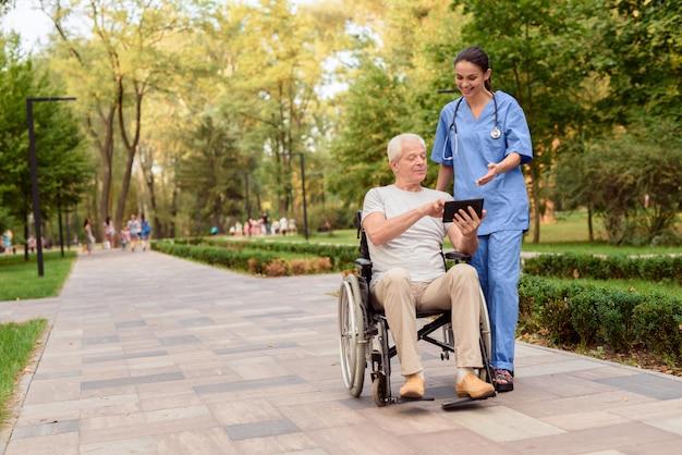 Homem sentado em uma cadeira de rodas e mostra enfermeira algo.