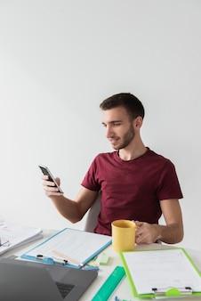 Homem sentado em uma cadeira e olhando para o celular