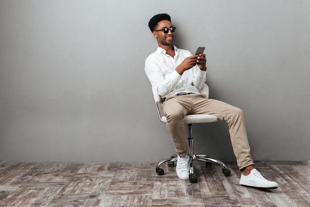 Homem sentado em uma cadeira e segurando o telefone móvel