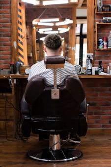 Homem sentado em uma cadeira, olhando no espelho