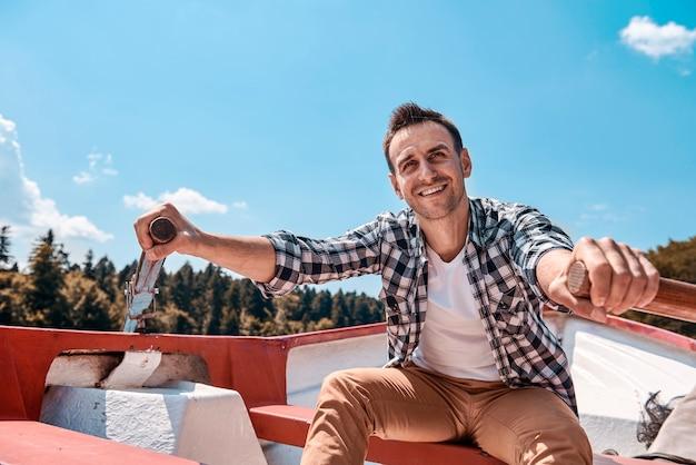 Homem sentado em uma canoa navegando no lago