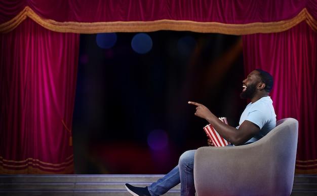 Homem sentado em uma poltrona assiste a um show em um teatro