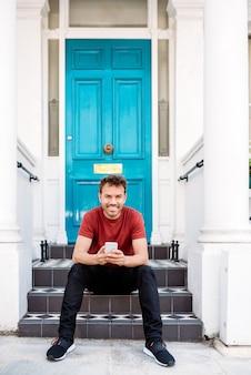 Homem sentado em uma porta azul com telefone móvel