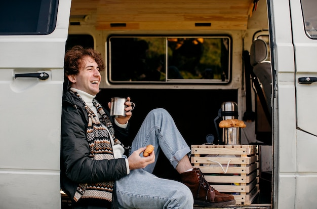 Homem sentado em uma van bebendo seu café