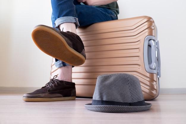 Homem sentado na bagagem