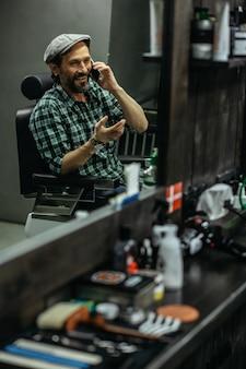 Homem sentado na barbearia e sorrindo enquanto tem uma conversa agradável ao telefone