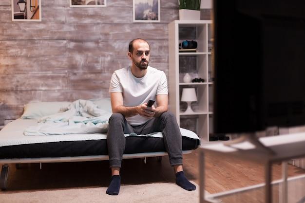 Homem sentado na beira da cama à noite, assistindo tv, segurando o controle remoto.
