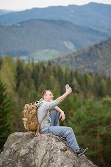 Homem sentado na beira de uma pedra e faz selfie no seu telefone