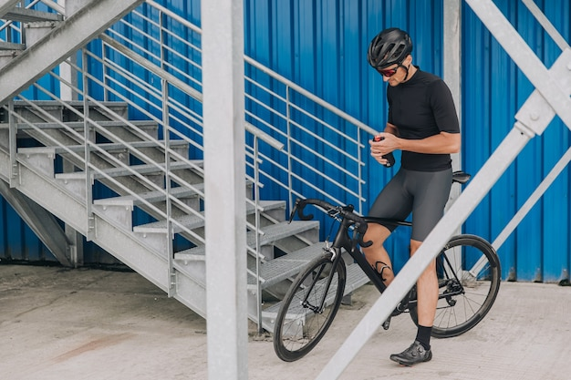 Homem sentado na bicicleta com uma garrafa de água nas mãos