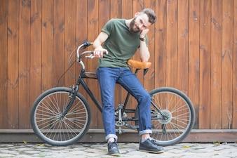 Homem sentado na bicicleta contra a parede de madeira