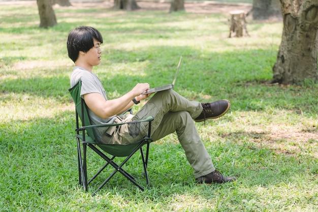 Homem sentado na cadeira de camping e trabalhando com o computador portátil no jardim