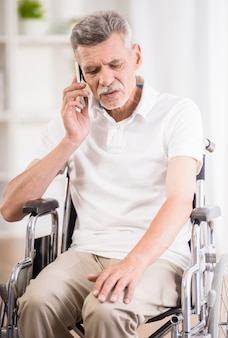 Homem sentado na cadeira de rodas em casa e falando no telefone.