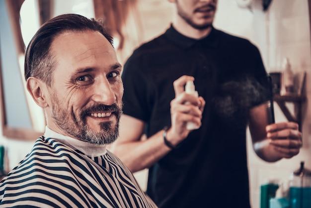 Homem sentado na cadeira em cortes na barbearia