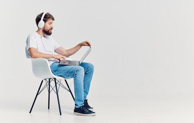 Homem sentado na cadeira na frente do laptop em fundo isolado de tecnologia de comunicação de fones de ouvido. foto de alta qualidade
