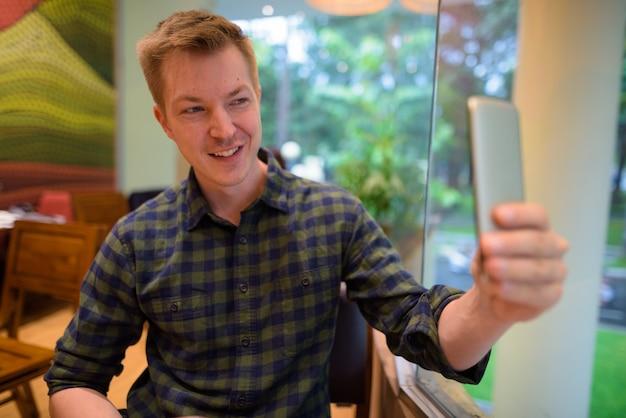 Homem sentado na cafeteria enquanto estiver usando o celular para tirar uma selfie