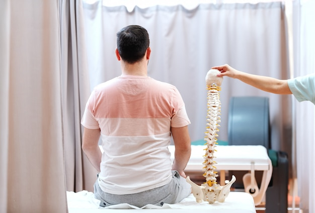 Homem sentado na cama de hospital com as costas viradas. ao lado dele médico segurando modelo de coluna vertebral.