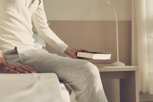 Homem sentado na cama deixando um livro na mesa de cabeceira