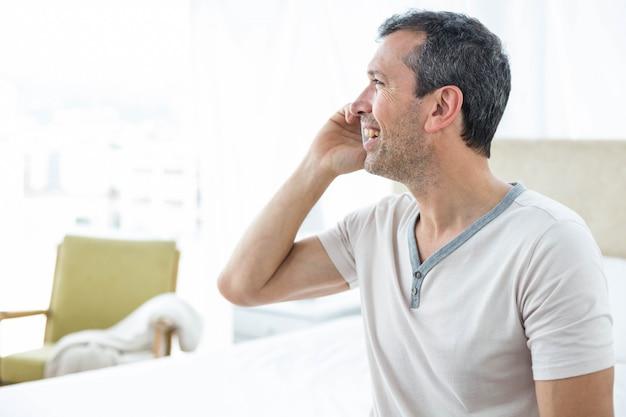 Homem sentado na cama e falando no smartphone no quarto