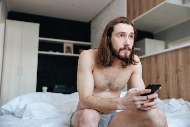Homem sentado na cama e usando telefone celular na manhã